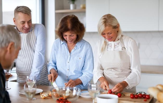 Vorderansicht einer gruppe fröhlicher älterer freunde bei der dinnerparty zu hause, kochen.