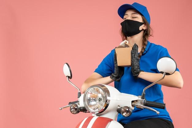 Vorderansicht einer hoffnungsvollen kurierin mit schwarzer medizinischer maske und handschuhen, die eine kleine schachtel auf pfirsichhintergrund hält