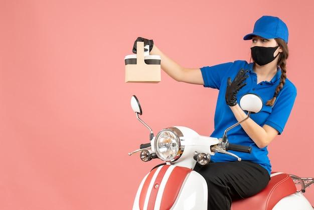 Vorderansicht einer hoffnungsvollen weiblichen lieferperson mit medizinischer maske und handschuhen, die auf einem roller sitzt und bestellungen auf pastellfarbenem pfirsichhintergrund liefert
