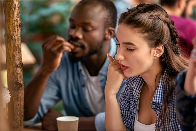 Vorderansicht einer jungen frau, die auf der terrasse eines gemütlichen restaurants ernsthaft auf die speisekarte schaut