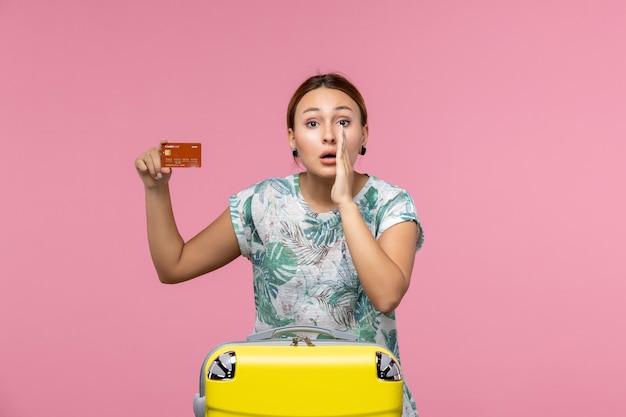 Vorderansicht einer jungen frau, die eine braune bankkarte hält und an einer rosa wand flüstert