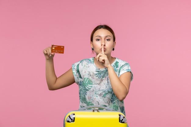 Vorderansicht einer jungen frau, die eine braune bankkarte hält und darum bittet, an einer rosa wand ruhig zu sein?