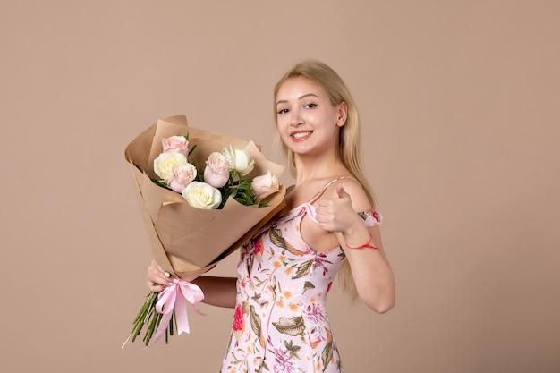 Vorderansicht einer jungen frau, die mit einem strauß schöner rosen an einer braunen wand posiert