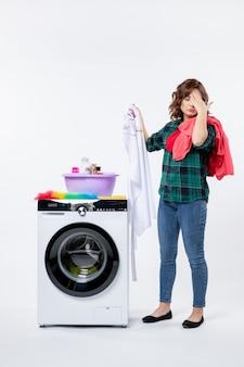 Vorderansicht einer jungen frau mit waschmaschine, die kleidung zum waschen an der weißen wand vorbereitet