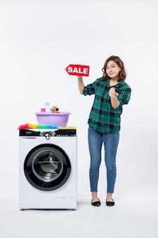 Vorderansicht einer jungen frau mit waschmaschine, die verkaufsschrift an der weißen wand hält