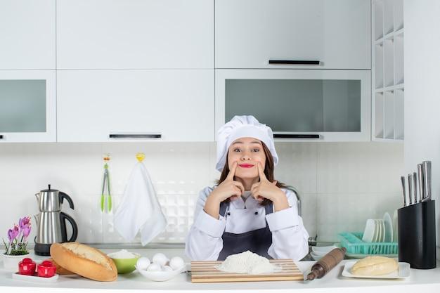 Vorderansicht einer jungen köchin in uniform, die hinter dem tisch steht, mit schneidebrett-lebensmitteln, die in der weißen küche eine lächelngeste machen?