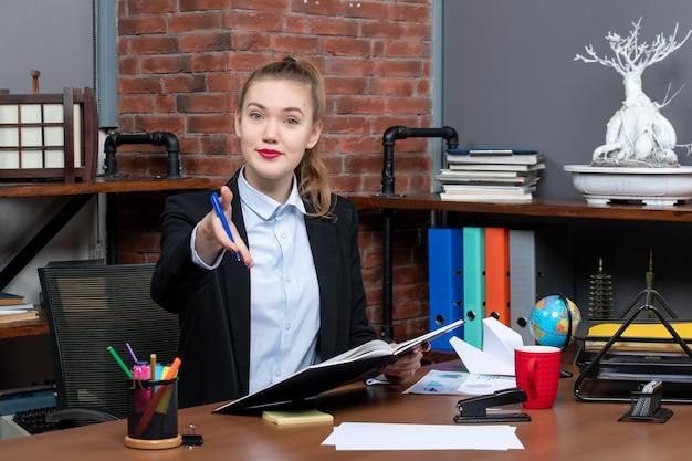 Vorderansicht einer jungen selbstbewussten assistentin, die an ihrem schreibtisch sitzt und ein dokument hält, das jemanden im büro begrüßt