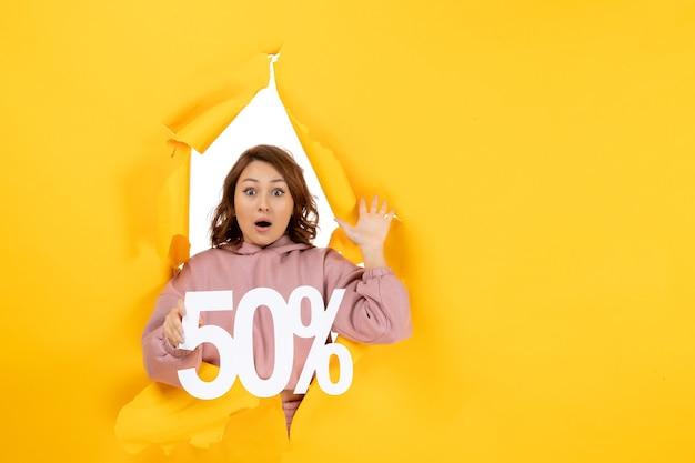 Vorderansicht einer jungen verwirrten dame, die ein fünfzigprozentzeichen auf gelbem riss zeigt