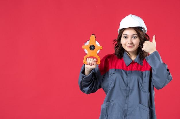 Vorderansicht einer lächelnden architektin in uniform mit schutzhelm, die maßband hält und eine ok geste auf isoliertem rotem hintergrund macht