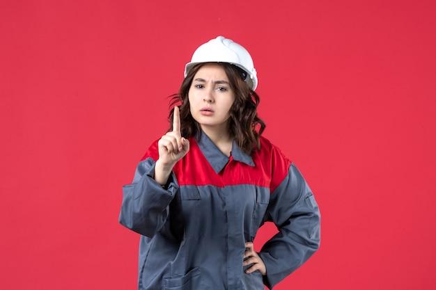Vorderansicht einer nervösen baumeisterin in uniform mit schutzhelm und nach oben auf isoliertem rotem hintergrund zeigend
