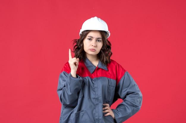 Vorderansicht einer neugierigen baumeisterin in uniform mit schutzhelm und nach oben auf isoliertem rotem hintergrund zeigend