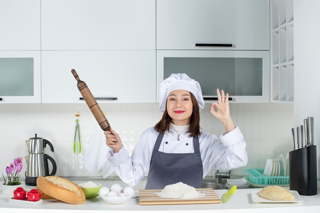 Vorderansicht einer selbstbewussten köchin in uniform, die hinter dem tisch steht, mit schneidebrett-lebensmitteln, die ein nudelholz halten und eine perfekte geste in der weißen küche machen
