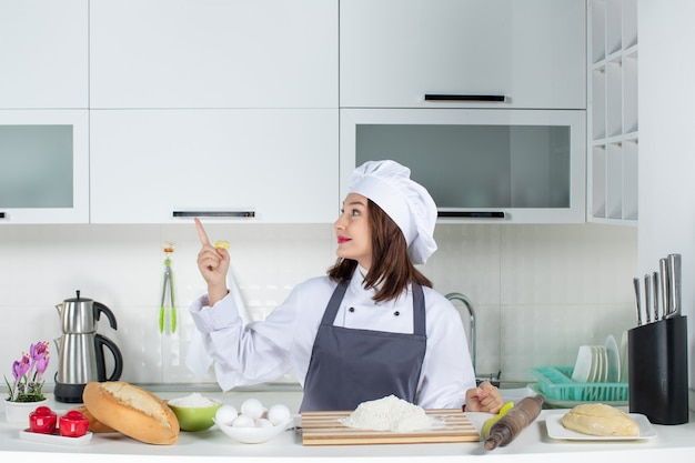 Vorderansicht einer selbstbewussten köchin in uniform, die hinter dem tisch steht, mit schneidebrettbrotgemüse, das in der weißen küche nach oben zeigt