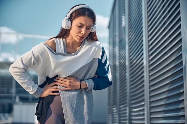 Vorderansicht einer traurigen sportlichen frau in drahtlosen kopfhörern, die an bauchschmerzen leidet