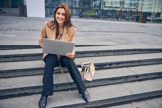 Vorderansicht einer übermütigen jungen geschäftsfrau mit ihrem laptop, die in die kamera lächelt