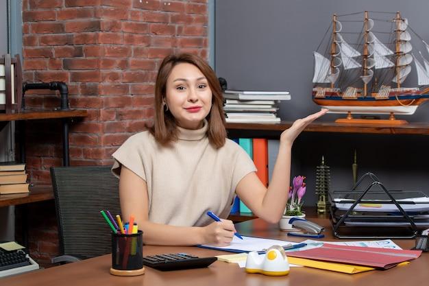 Vorderansicht einer zufriedenen geschäftsfrau, die auf etwas zeigt, das an der wand sitzt