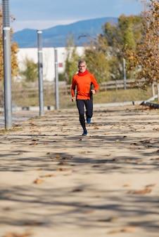 Vorderansicht eines älteren mannes in der sportkleidung, die in einem stadtpark an einem sonnigen tag rüttelt