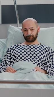 Vorderansicht eines afroamerikanischen facharztes und eines kranken mannes, der während der krankheitsberatung in der krankenstation eine online-videokonferenz mit dem arzt hat