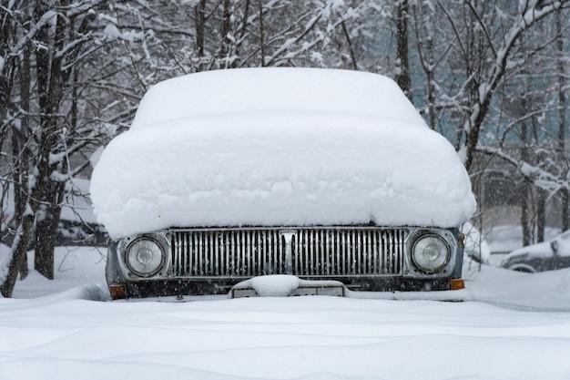 Vorderansicht eines alten sowjetischen autos bedeckt mit schnee nach schneesturm im moskauer hof