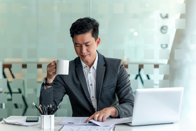 Vorderansicht eines asiatischen geschäftsmannes, der kaffee trinkt, während er den im büro platzierten dokumentenlaptop überprüft.