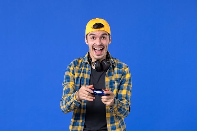 Vorderansicht eines aufgeregten männlichen spielers mit gamepad, der videospiele an blauer wand spielt