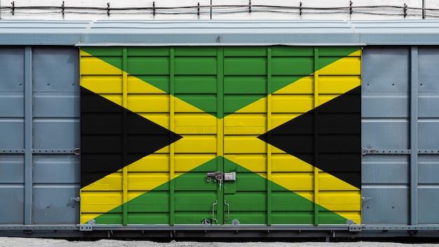 Vorderansicht eines containerzuggüterwagens mit einem großen metallverschluß mit der staatsflagge von jamaika das konzept des exports - import, des transportes, der nationalen lieferung von waren und des schienentransports
