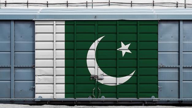 Vorderansicht eines containerzuggüterwagens mit einem großen metallverschluß mit der staatsflagge von pakistan das konzept des exports und des imports, des transportes, der nationalen lieferung von waren und des schienentransports