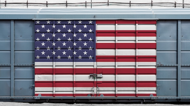 Vorderansicht eines containerzuggüterwagens mit einem großen metallverschluß mit der staatsflagge von usa das konzept des exportimports, des transportes, der nationalen lieferung von waren und des schienentransports