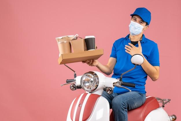 Vorderansicht eines dankbaren männlichen lieferers in maske mit hut, der auf einem roller sitzt und bestellungen auf pfirsichhintergrund liefert