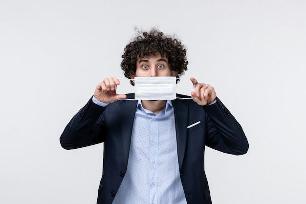 Vorderansicht eines emotionalen männlichen unternehmers im anzug und herunterziehen seiner maske auf weißer oberfläche