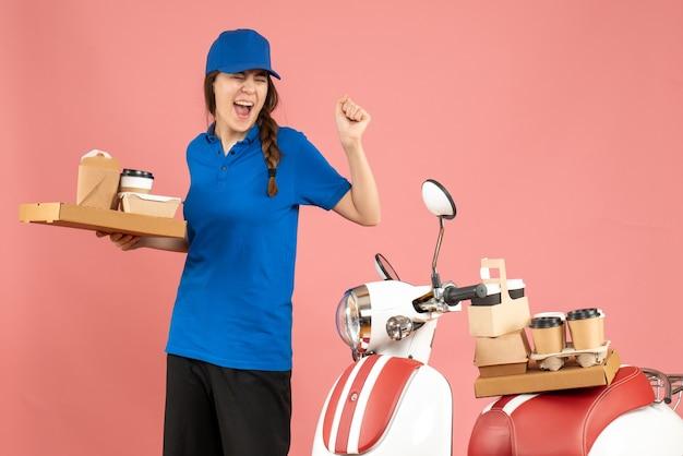 Vorderansicht eines emotionalen stolzen kuriermädchens, das neben dem motorrad steht und kaffee und kleine kuchen auf pastellfarbenem pfirsichhintergrund hält