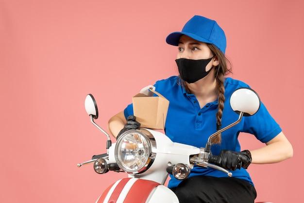 Vorderansicht eines fokussierten weiblichen kuriers mit schwarzer medizinischer maske und handschuhen, die eine kleine schachtel auf pfirsichhintergrund halten