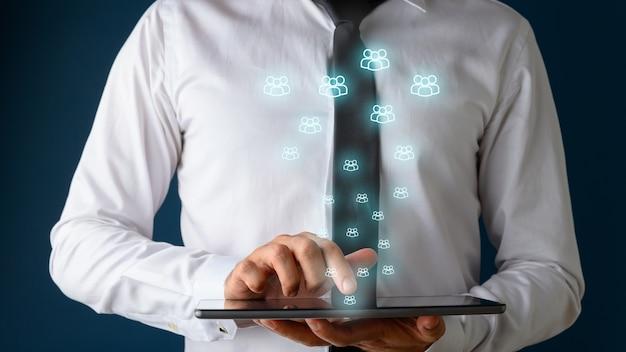 Vorderansicht eines geschäftsmannes, der digitales tablet mit vielen leuchtenden personenikonen verwendet, die aus ihm herauskommen