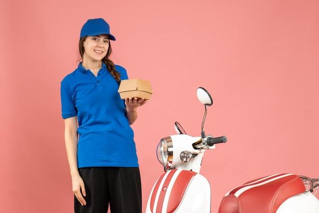 Vorderansicht eines glücklichen kuriermädchens, das neben dem motorrad steht und kuchen auf pastellfarbenem pfirsichhintergrund hält