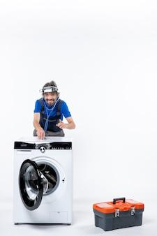 Vorderansicht eines glücklichen mechanikers mit stirnlampe, der das stethoskop auf die waschmaschine auf die weiße wand legt