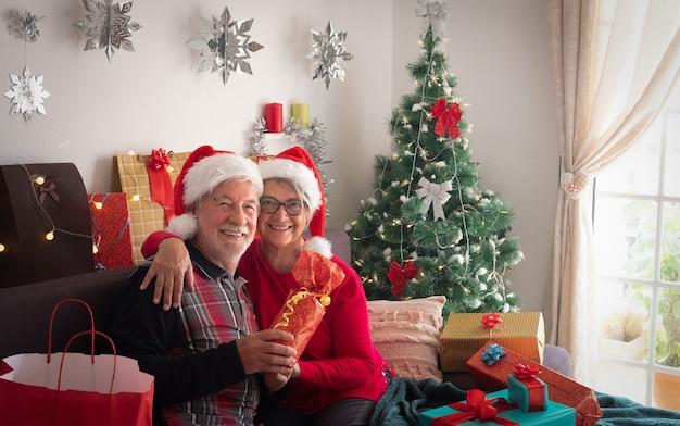 Vorderansicht eines glücklichen paares älterer leute, die weihnachtsmützen tragen und die kamera betrachten. viele weihnachtsgeschenke in ihrer nähe für familie und freunde.