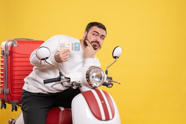 Vorderansicht eines jungen denkenden reisenden mannes, der auf einem motorrad mit einem koffer darauf sitzt und ein ticket auf isoliertem gelbem hintergrund hält