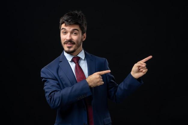 Vorderansicht eines jungen emotional lächelnden mannes im anzug, der auf eine isolierte dunkle wand zeigt