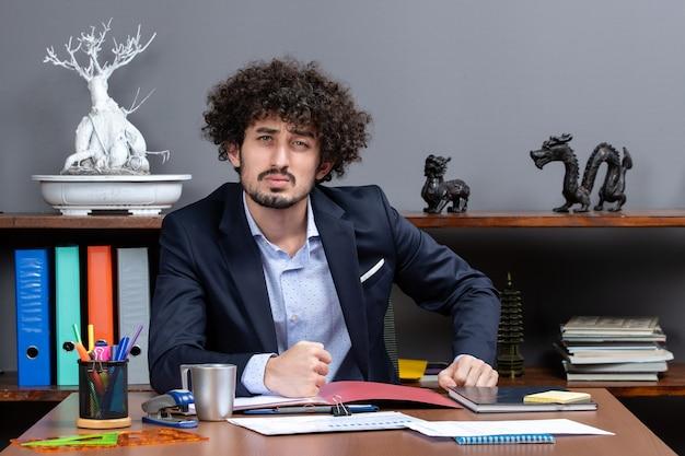 Vorderansicht eines jungen geschäftsmannes, der im modernen büro am schreibtisch sitzt
