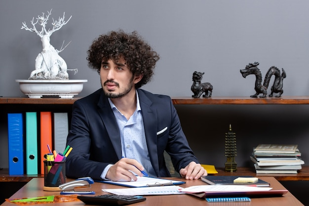 Vorderansicht eines jungen geschäftsmannes im anzug, der am schreibtisch im büro sitzt