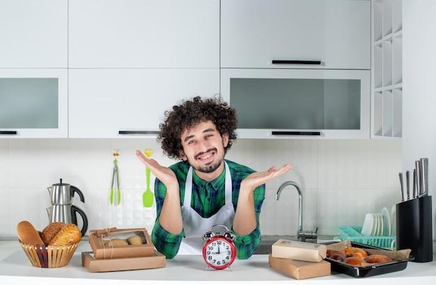 Vorderansicht eines jungen lächelnden mannes, der in der weißen küche hinter der tischuhr steht, verschiedene backwaren darauf