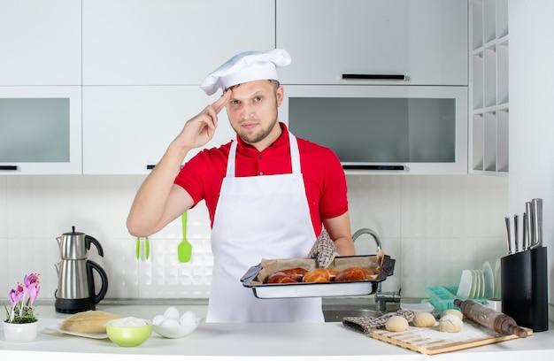 Vorderansicht eines jungen männlichen kochs mit halter, der frisch gebackenes gebäck hält und sich stolz in der weißen küche fühlt