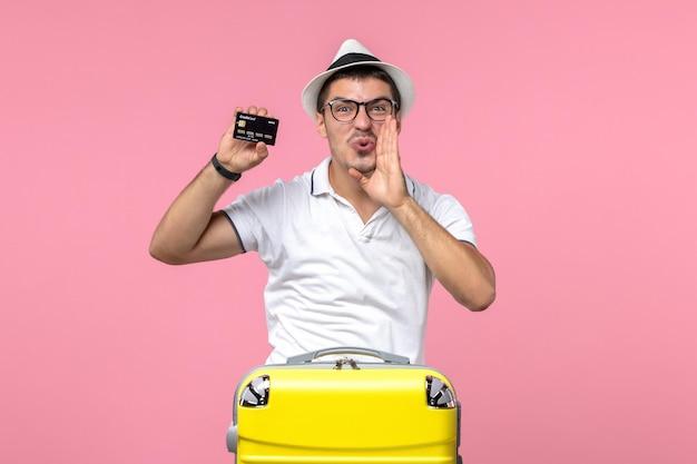 Vorderansicht eines jungen mannes, der emotional eine schwarze bankkarte an der rosa wand hält