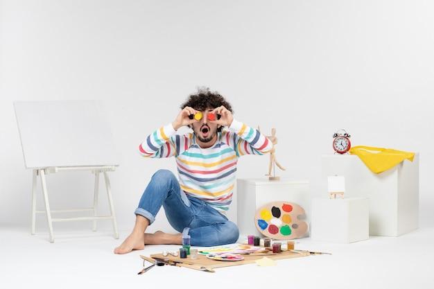 Vorderansicht eines jungen mannes, der farben zum zeichnen in kleinen dosen auf weißer wand hält