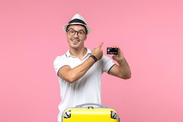 Vorderansicht eines jungen mannes, der im urlaub eine bankkarte hält und auf einer rosa wand lächelt