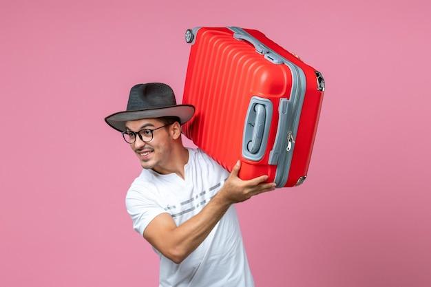 Vorderansicht eines jungen mannes, der in den urlaub geht und eine rote tasche an der rosa wand hält