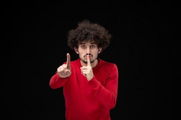 Vorderansicht eines jungen mannes im roten hemd, der auf der schwarzen wand um schweigen bittet