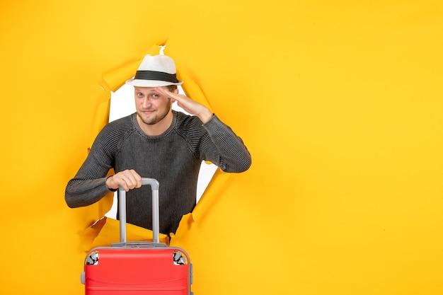 Vorderansicht eines jungen mannes mit einem hut, der eine tasche hält und in einer zerrissenen gelben wand hallo sagt