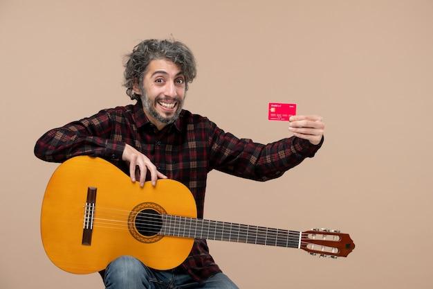 Vorderansicht eines jungen mannes mit gitarre, der eine rote bankkarte an einer rosa wand hält