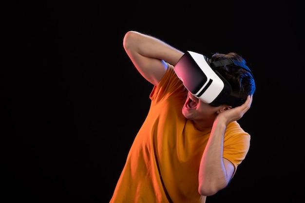 Vorderansicht eines jungen mannes mit vr-headset an der dunklen wand
